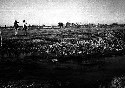 Hombres conversando cerca de un ojo de agua en las Palosmas, Chihuahua