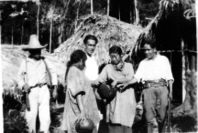 Mujeres tzotziles conversan con hombres cerca de sus chozas