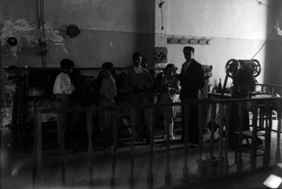 Niños y hombres reparan calzado en un taller