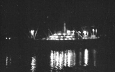 Barco anclado en un puerto, toma nocturna