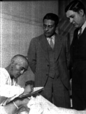Hombre herido en la cama de un Hospital firmando documentos anta agentes del Ministerio Publico