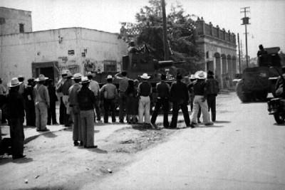 Hombres observando transporte militar y artillería por una calle