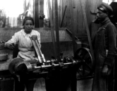 Obreros operando una máquina durante la fabricación de monedas