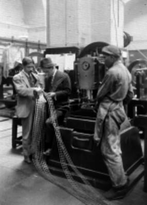 Obrero mostrando troqueles de la fabricación de monedas