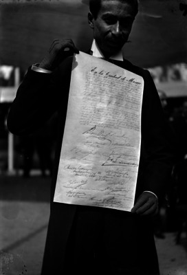 Hombre muestra bando que simboliza la conmemoración del Centenario de la Independencia