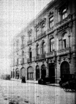 Gente y automoviles frente a un edificio público