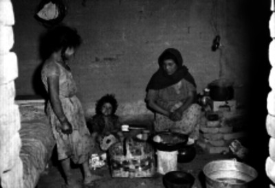 Mujer con niños en el interior de una choza