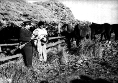 Policía y campesino en el establo de una hacienda