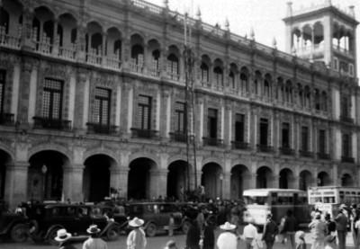 Gente y automoviles frente al edificio del Ayuntamiento