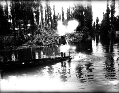 Hombre a bordo de una canoa navega por un canal de Xochimilco