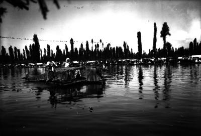 Indígenas abordo de una trajinera con forma de avión, navegando por un canal de Xochimilco, durante una festividad