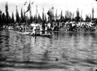 Gente a la orilla de un canal de Xochimilco durante una carrera de canotaje