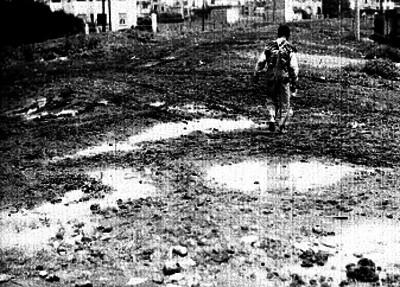 Hombre caminando en un terreno baldío