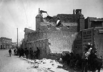 Gente junto a casa destruida por los enfrentamientos durante la Decena Trágica