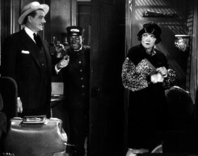 Pareja entra a una habitación del hotel acompañados de un botones negro, escena de película
