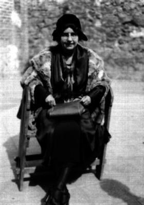 Mujer con sombrero sentada en una silla