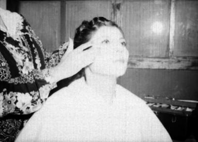 Maquillista arreglando a una mujer en una habitación