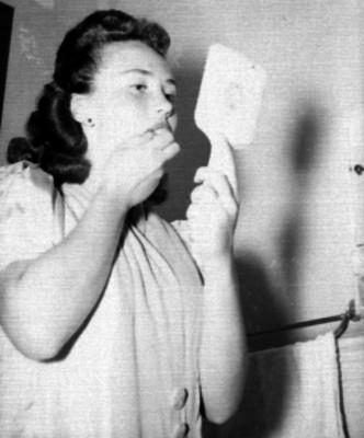 Mujer maquillandose en un baño