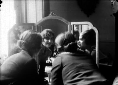 Mujeres maquillandose frente a un espejo