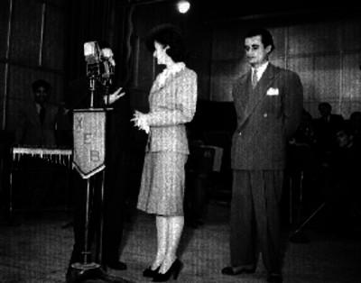 Locutor conversando con una mujer ante los micrófonos de la XEB