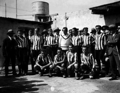 Integrantes de un equipo futbolístico y hombres, retrato de grupo