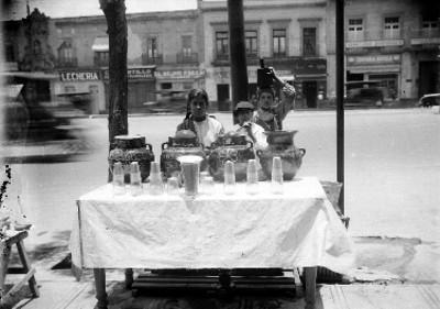 Niños despachan puesto de aguas frescas sobre la banqueta