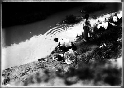 Mujeres lavan ropa en la orilla de río