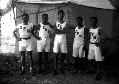 Atletas del equipo SEM junto a una tienda de campaña, retrato