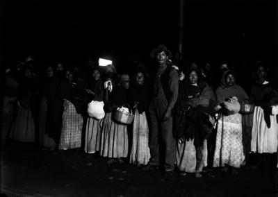 Mujeres y hombres en una fila para adquirir artículos de primera necesidad
