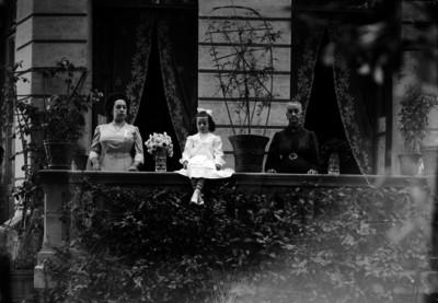 Anciana, mujer y niña en un balcón, retrato