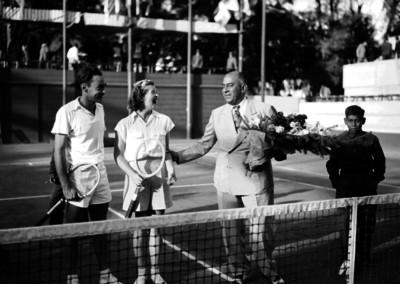 Tenistas con raqueta y hombre con flores, retrato de grupo