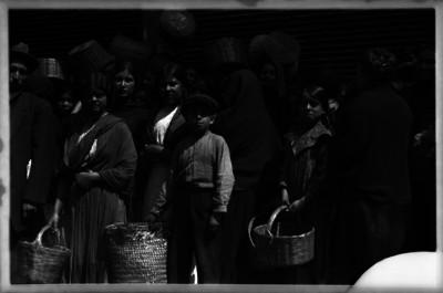 Mujeres y niños aguardan en fila para conseguir productos de primera necesidad