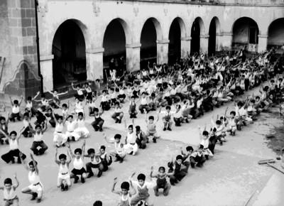 Niños práctican una tabla gimnástica en el patio de una escuela