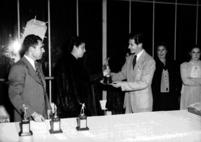 Bolichista recibe trofeo de manos de una mujer