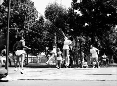 Mujeres saltan para pegarle al balón durante un encuentro de voleibol