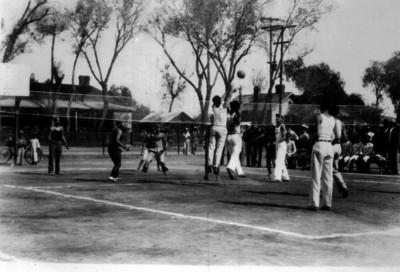 Deportistas saltan para pegarle al balón durante un partido de voleibol
