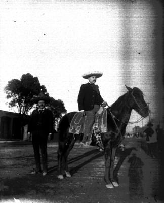Charro montado a caballo y hombre en una calle, retrato
