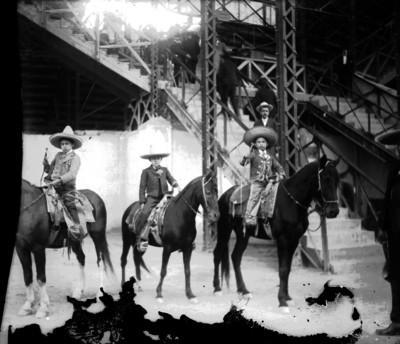 Niños charros a caballo junto a las tribunas, retrato