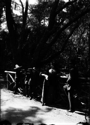 Hombre, mujer y niños se recargan en barandal de un parque
