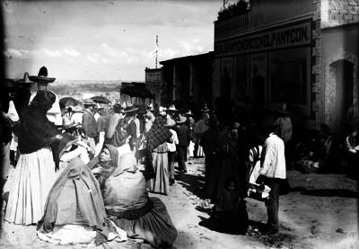 """Gente reunida frente a la pulquería """"Don Juan Tenorio en el Panteón"""" en la calle de un poblado"""