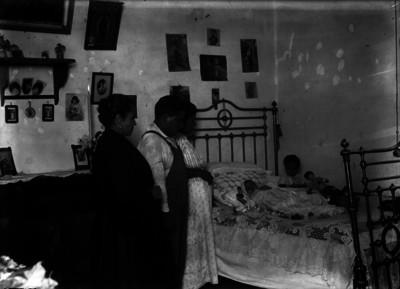 Grupo familiar vela a un niño, interior de habitación