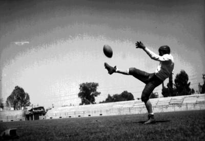 Atleta de futbol americano pátea balón en un entrenamiento