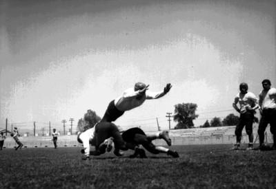 Atletas de futbol americano se lanzan al piso durante un entrenamiento