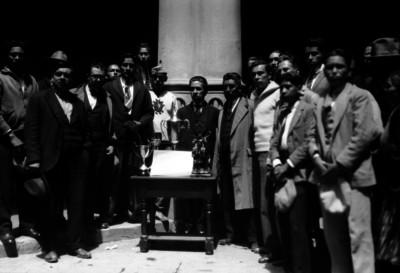 Alfonso Pruneda y funcionarios junto a la mesa de trofeos, retrato de grupo