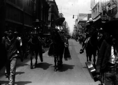 China poblana y charros a caballo desfilan por una calle