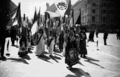 Mujeres con trajes folclóricos portan diversas banderas en un desfile