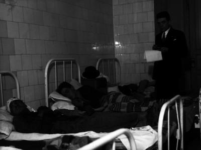 Agente del ministerio público junto a enfermos en la sala de un hospital