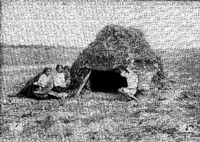 Familia indígena afuera de un jacal en un llano