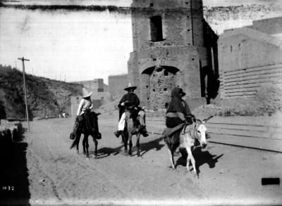 Hombres a caballo y mujer sobre asno, pasan por calle de un poblado