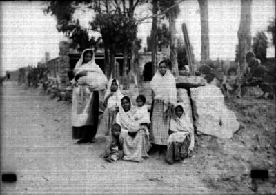 Mujeres y niños indígenas a la orilla de un camino